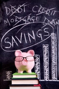 Piggy bank with savings chart on black board