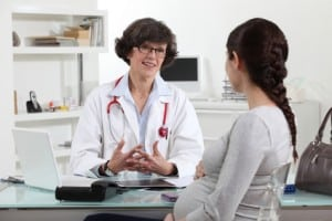 Pregnant woman in doctors midwife appointment