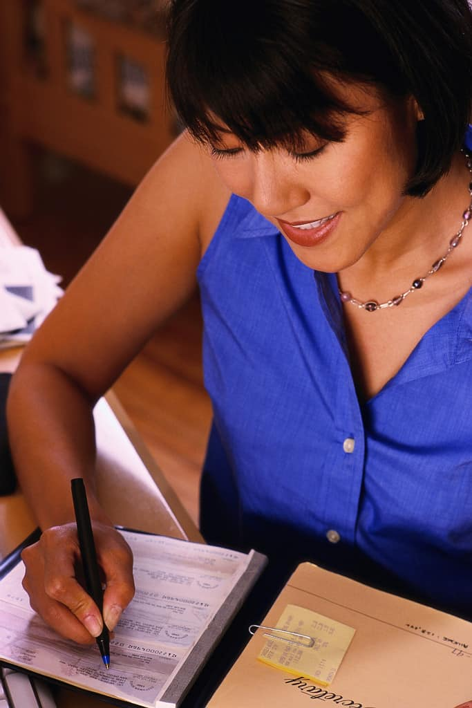 Asian woman writing a cheque